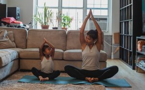 Mother and daughter doing yoga from home.